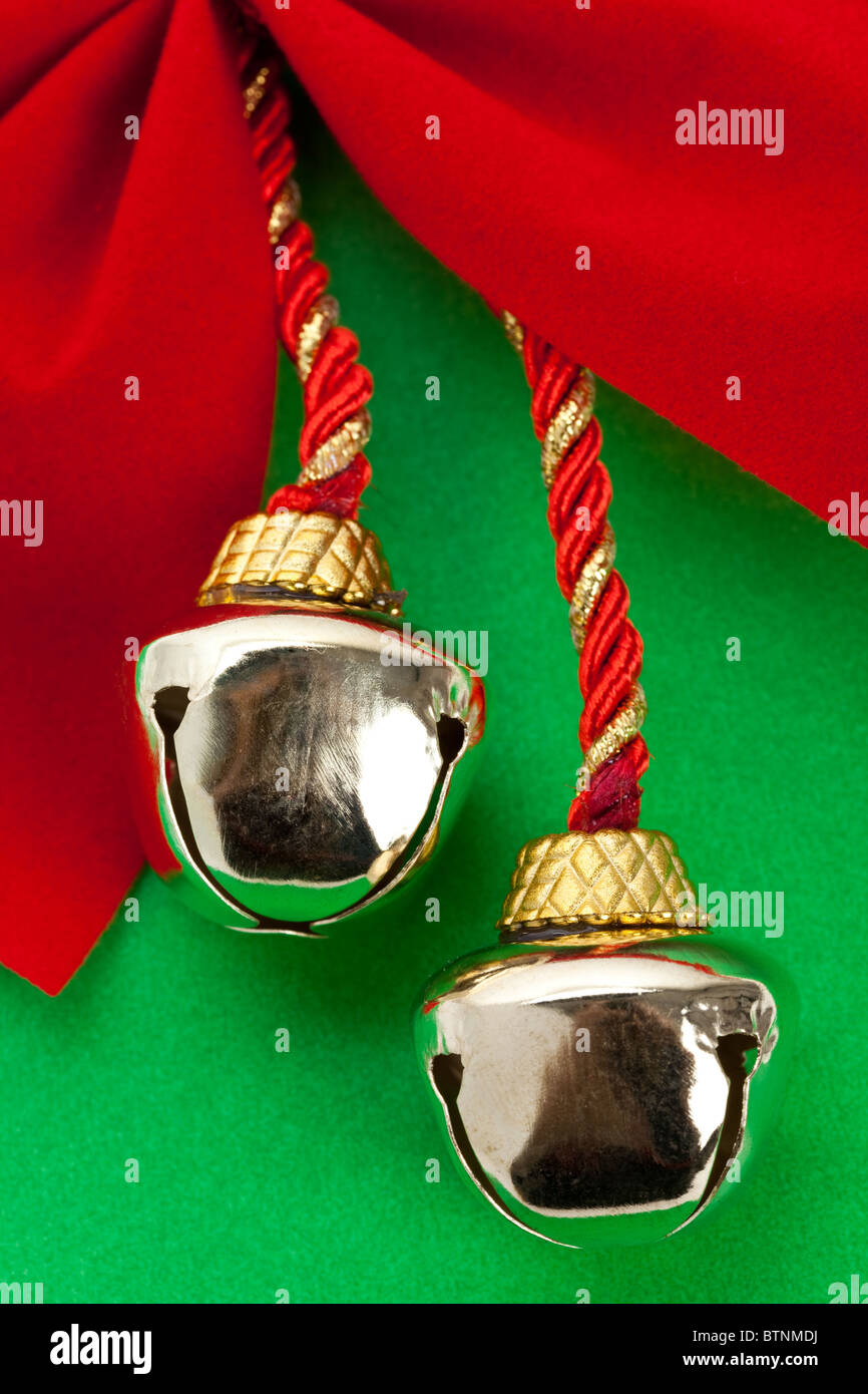 Christmas Bells and ribbon with green background - Stock Image