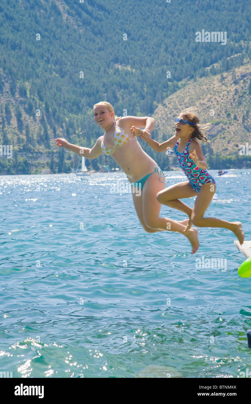 Sisters jumping off dock into lake Stock Photo