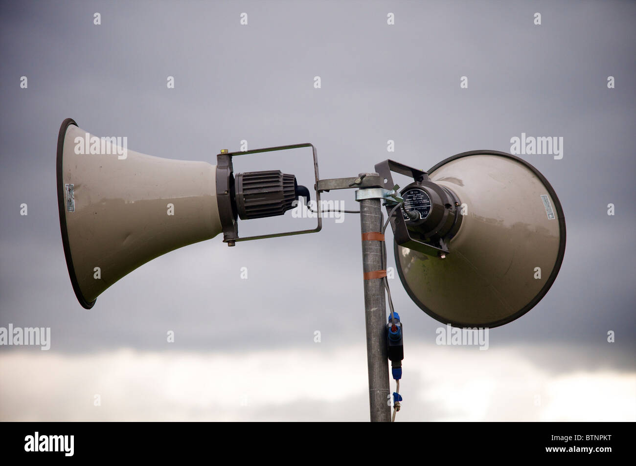 Close up of outdoor public address system against a grey sky - Stock Image