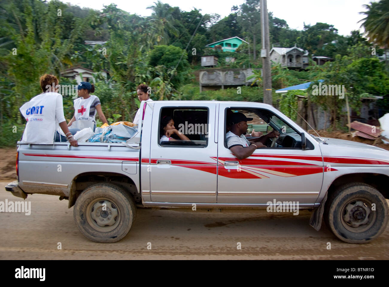 Red Cross and CDRT volunteers riding at back of pickup van after hurricane Tomas St Lucia - Stock Image
