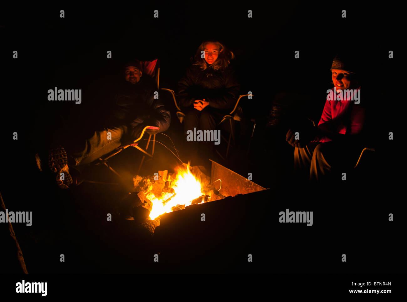 Group of friends sitting around a camp fire. - Stock Image
