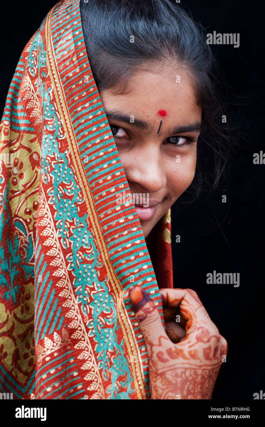 Indian girl wearing traditional silk sari with henna hands. India. Face portrait - Stock Image