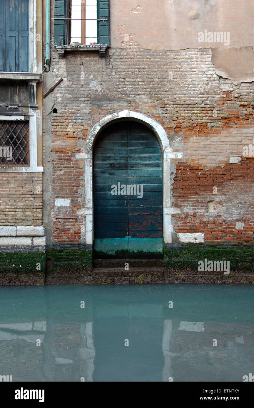 A decrepit / ramshackle doorway and canal in Venice Italy - Stock Image