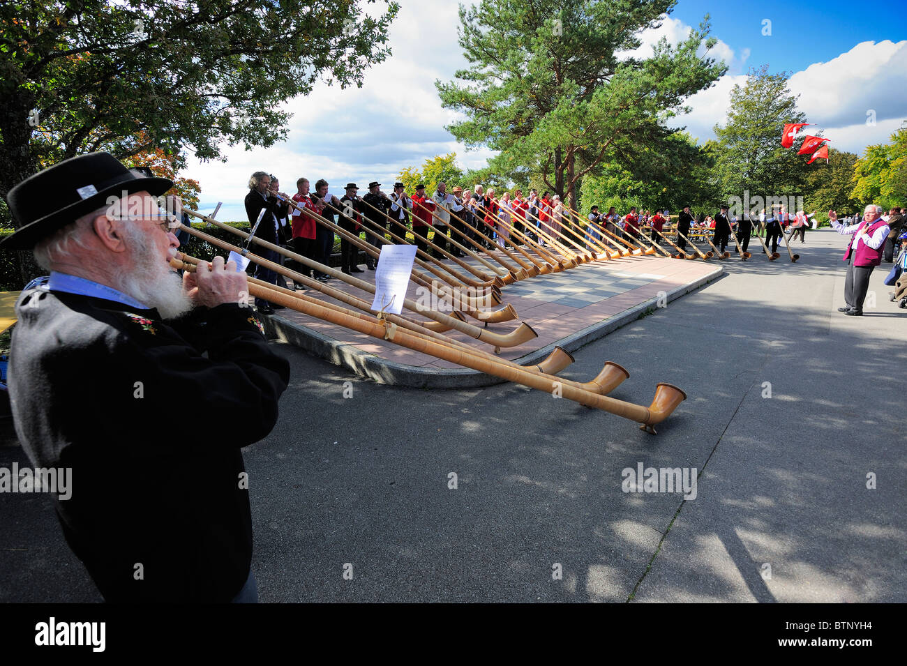 A large ensemble of Swiss alphorn players with traditional flag throwing taking place in the background - Stock Image