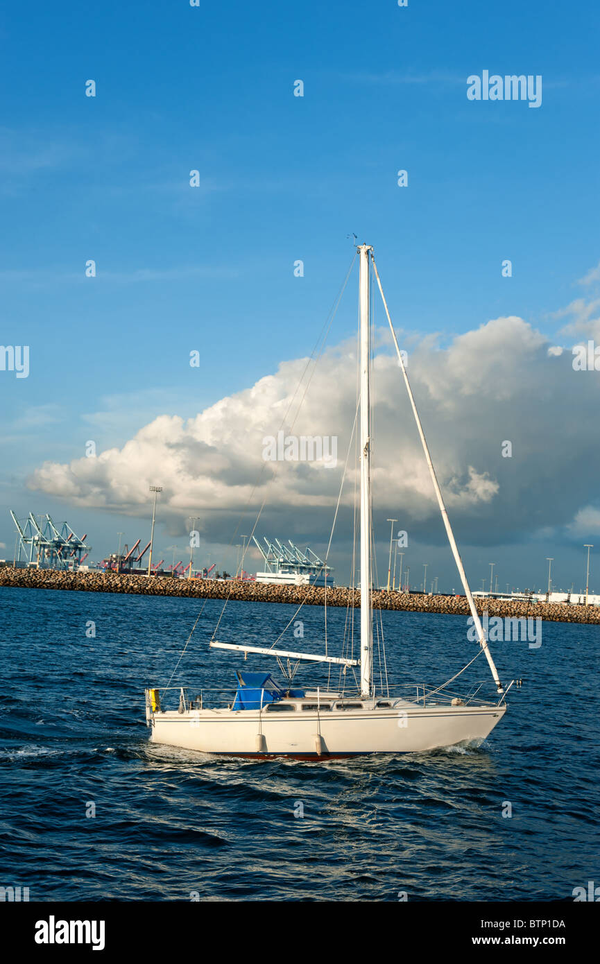 A sailboat cruising across the waters of a sunny waterfront. - Stock Image