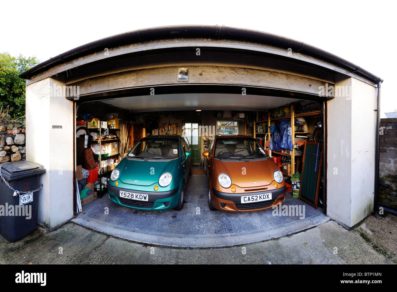 Two small Daewoo Matiz cars parked in domestic double garage Stock