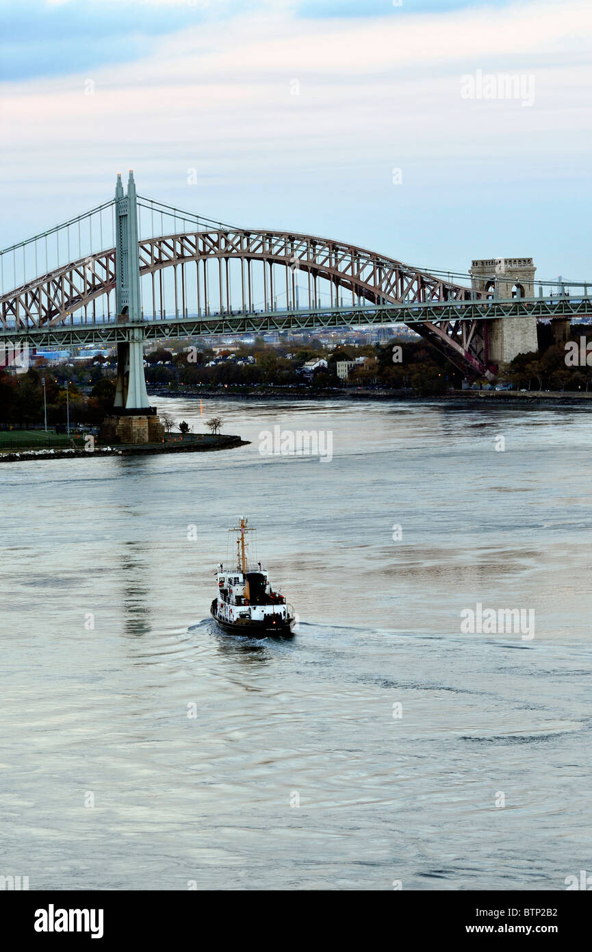 Police Tugboat approaching the Triborough (RFK) (Robert F. Kennedy) Bridge at Twilight - Stock Image