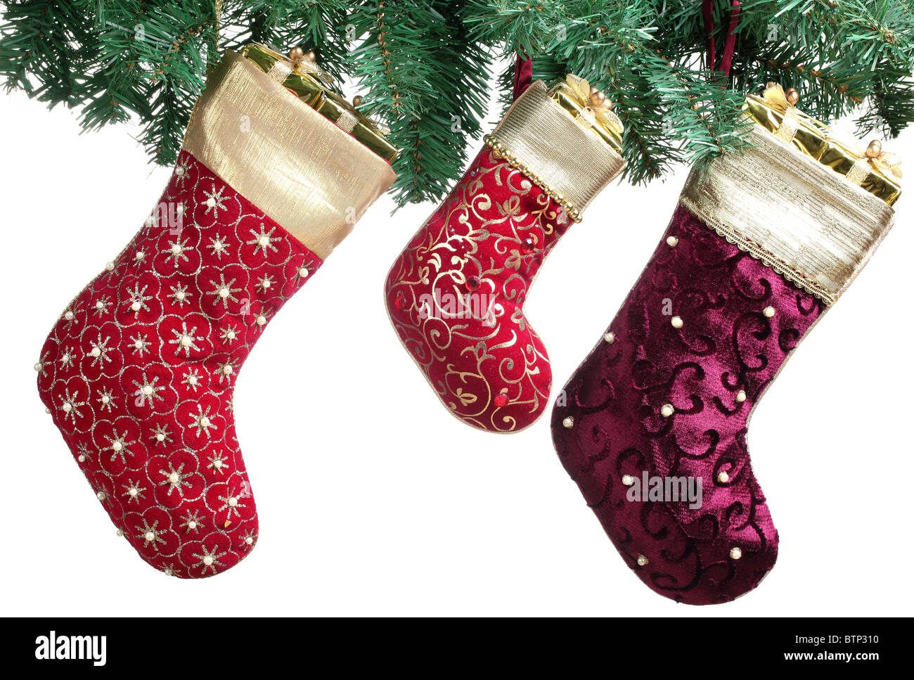 Christmas stocking with green spruce branch hanging over white background. - Stock Image