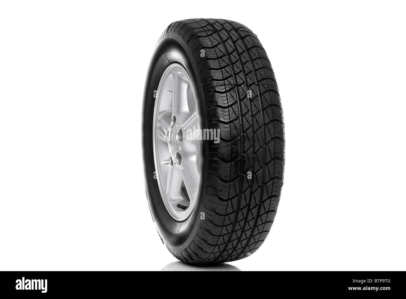 Photo of a car tyre (tire) on a five spoke alloy wheel isolated on a white background - Stock Image