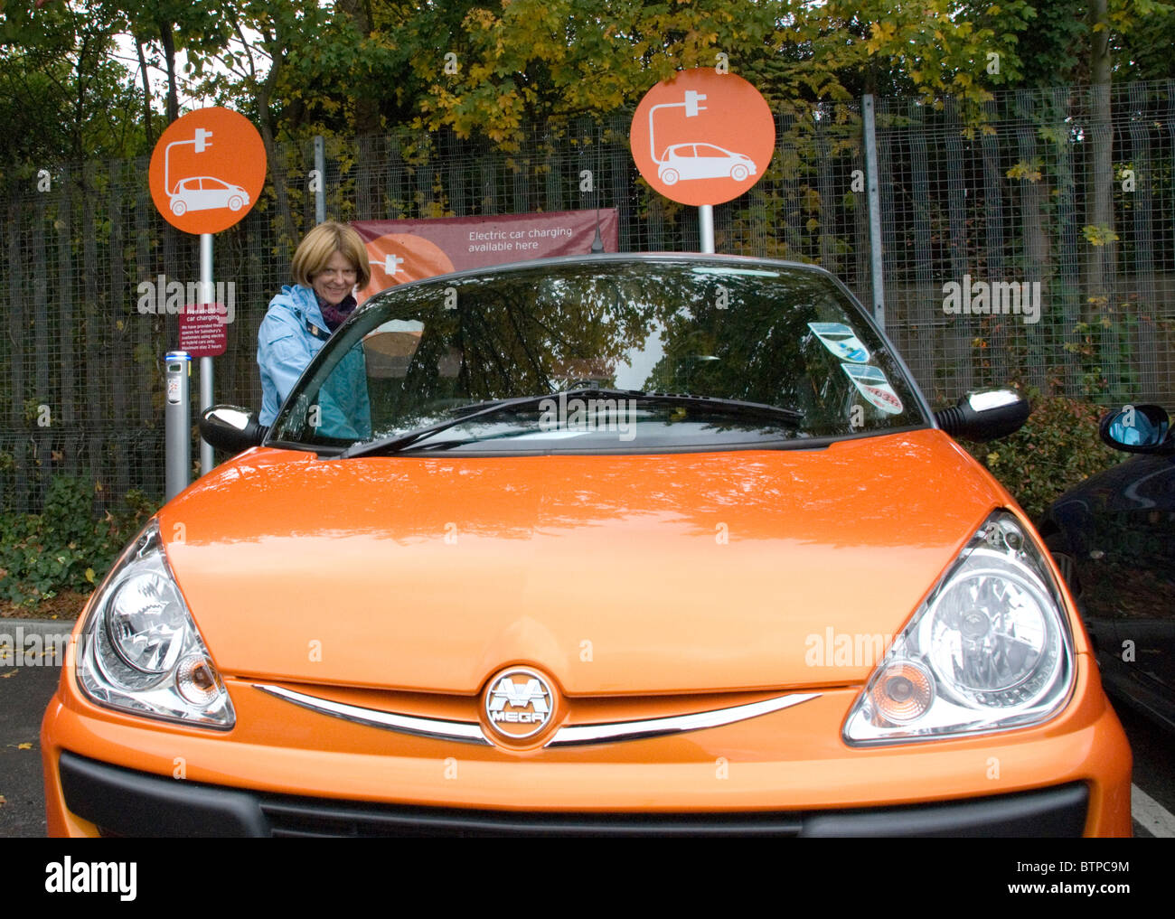 Woman getting in to electric car rented from GoGo Electric Cars free EV Elektrobay charging point Sainsbury's London - Stock Image