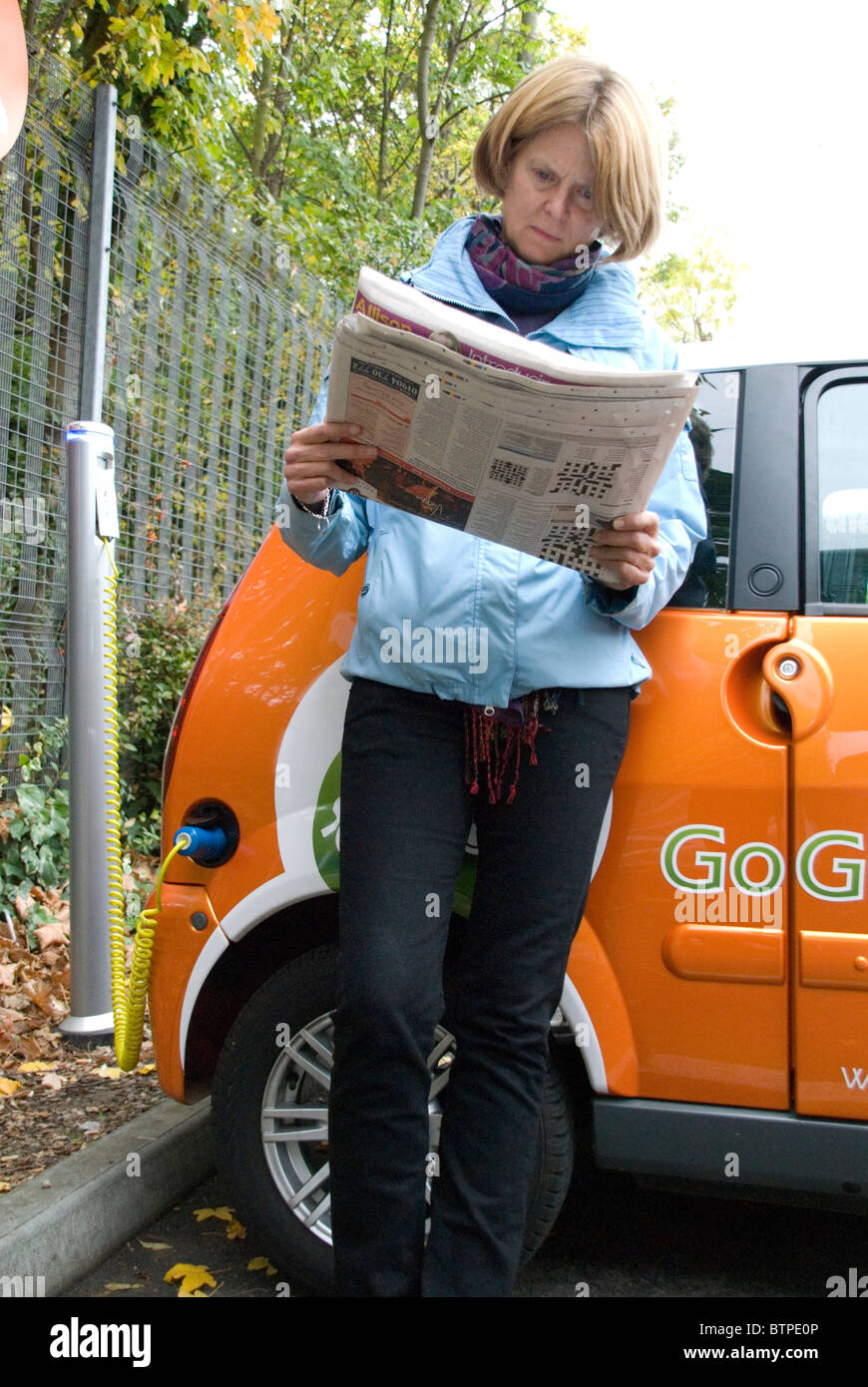 Woman reading paper waiting for car to charge Electric Cars free EV Elektrobay charging point Sainsbury's London - Stock Image