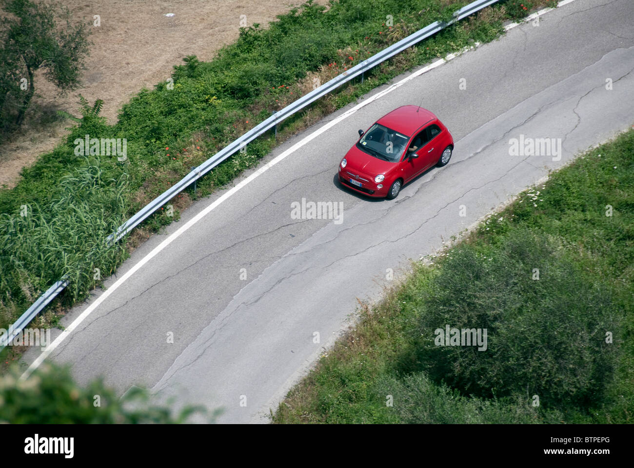 Small red Fiat 500 (model launched 2008) viewed from above on a road in Italy but could be anywhere. Man's arm - Stock Image