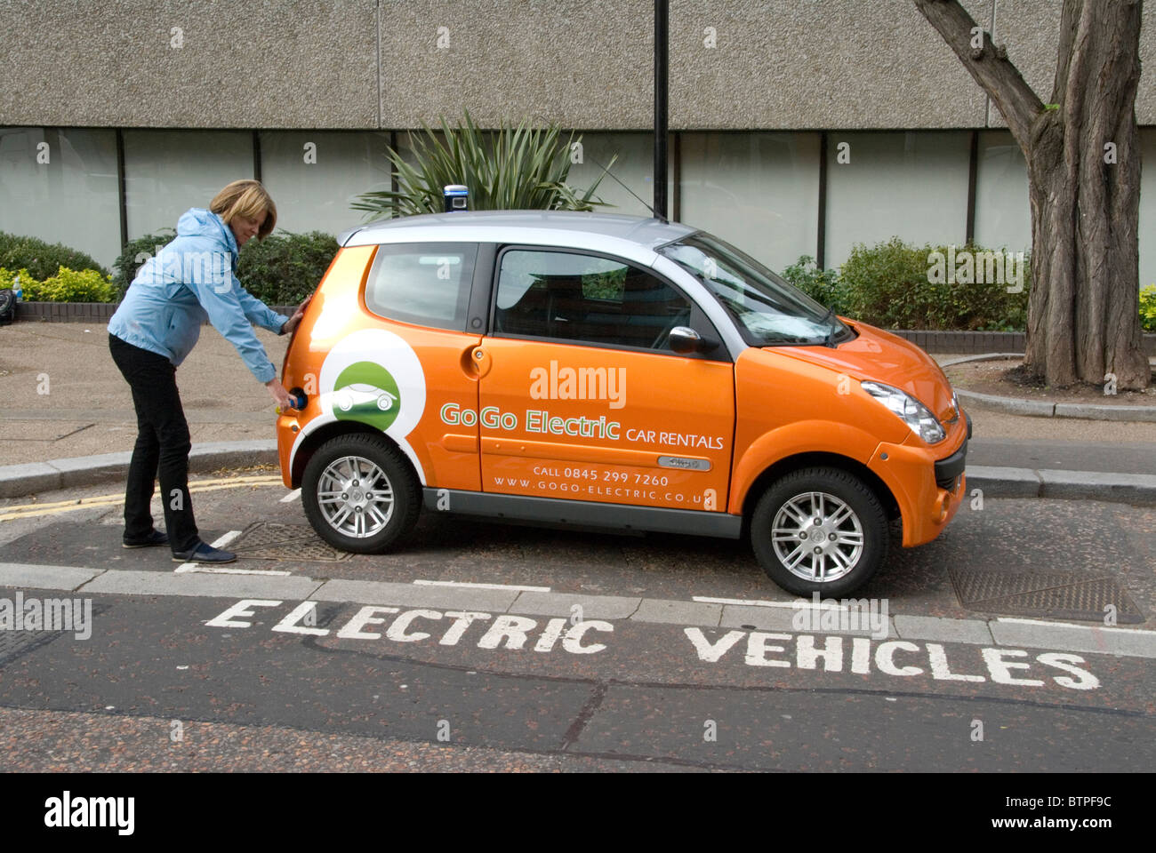 Woman plugging in electric vehicle at free EV charge point South Bank London UK GoGo Electric Vehicles rental - Stock Image