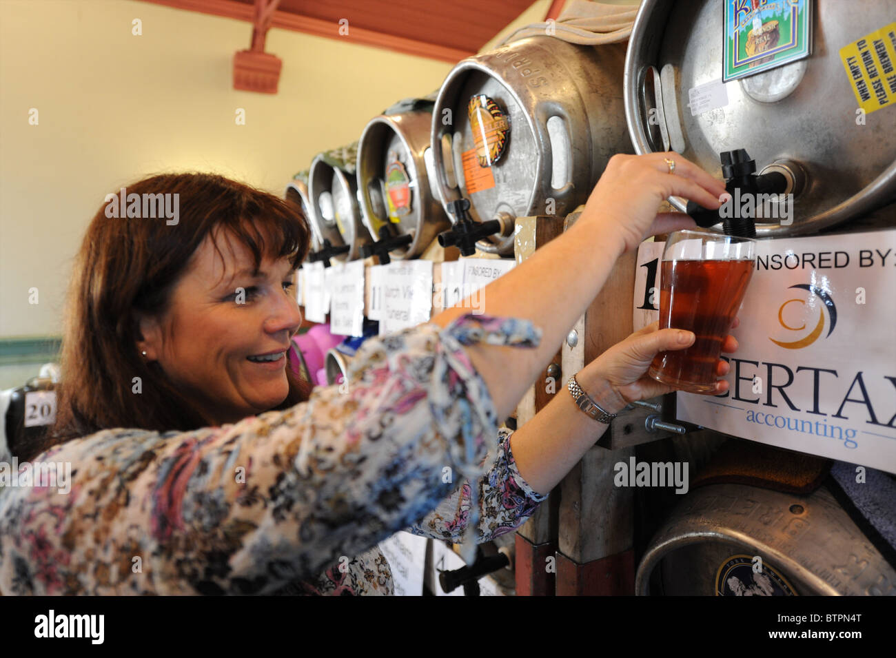 Barmaid fills pint glass from barrel at real ale festival - Stock Image