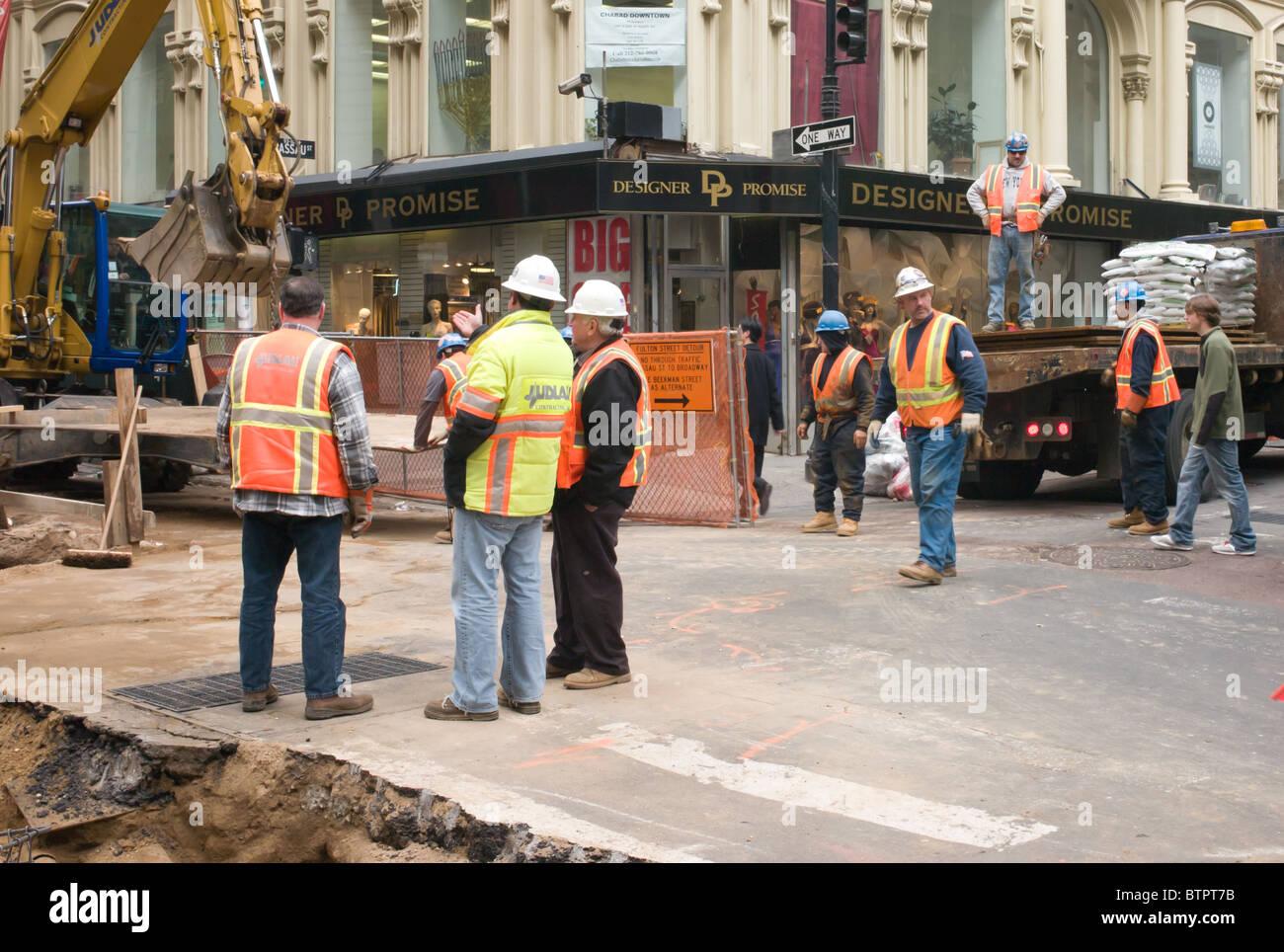 A street repair crew works in lower Manhattan in New York City, New York. - Stock Image