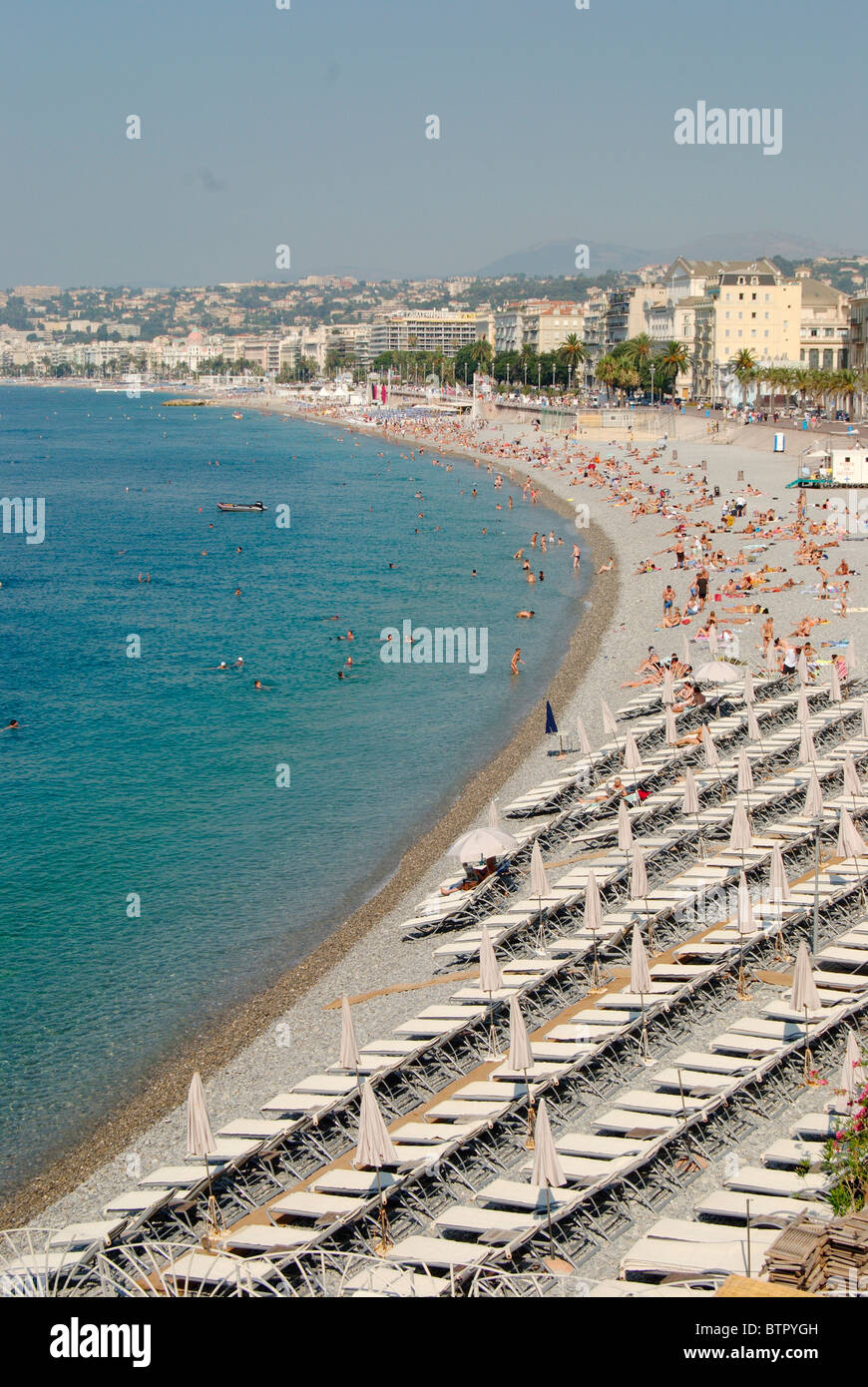 France, Nice, Promenade des Anglais, Large number of sun loungers and people at beach and city in background - Stock Image