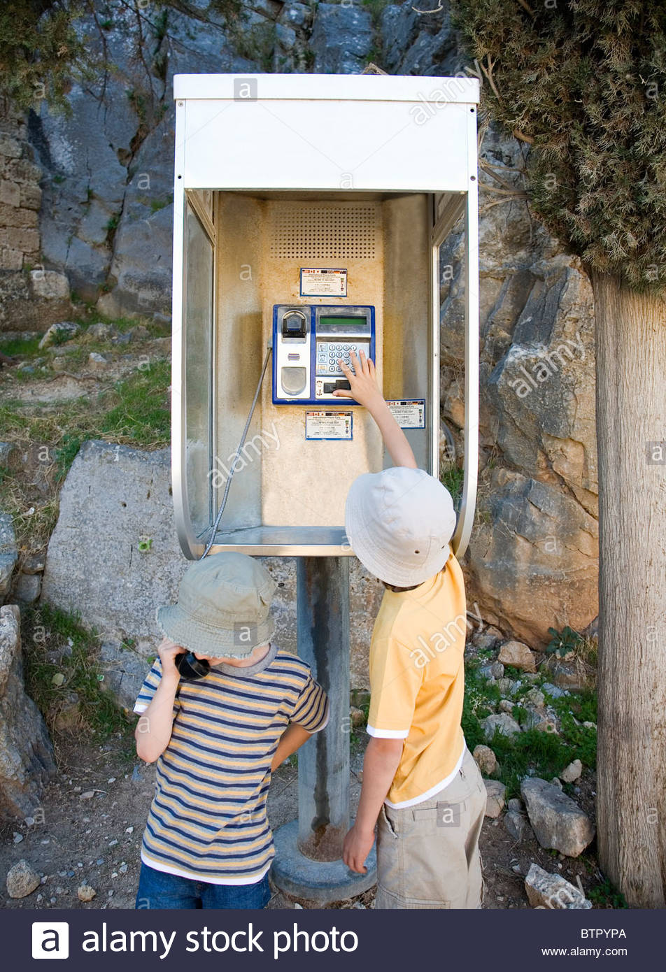 Two boys on phone in public phone box - Stock Image