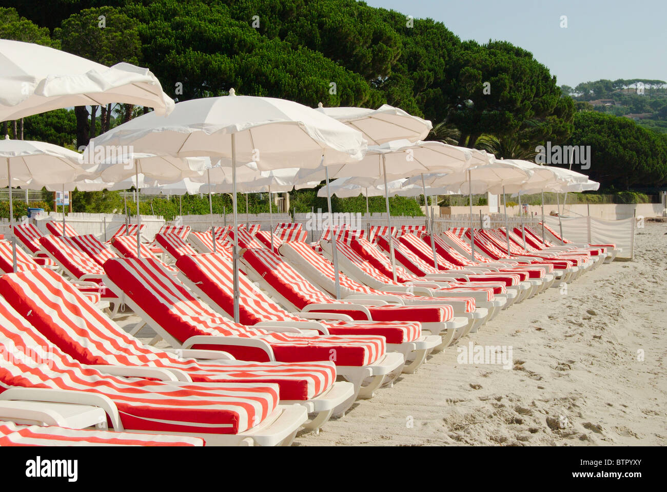 France, Saint-Tropez, Pampelonne, View of empty sun loungers and beach umbrellas at beach - Stock Image