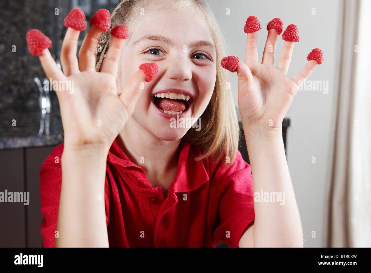 Girl with raspberries on fingers Stock Photo