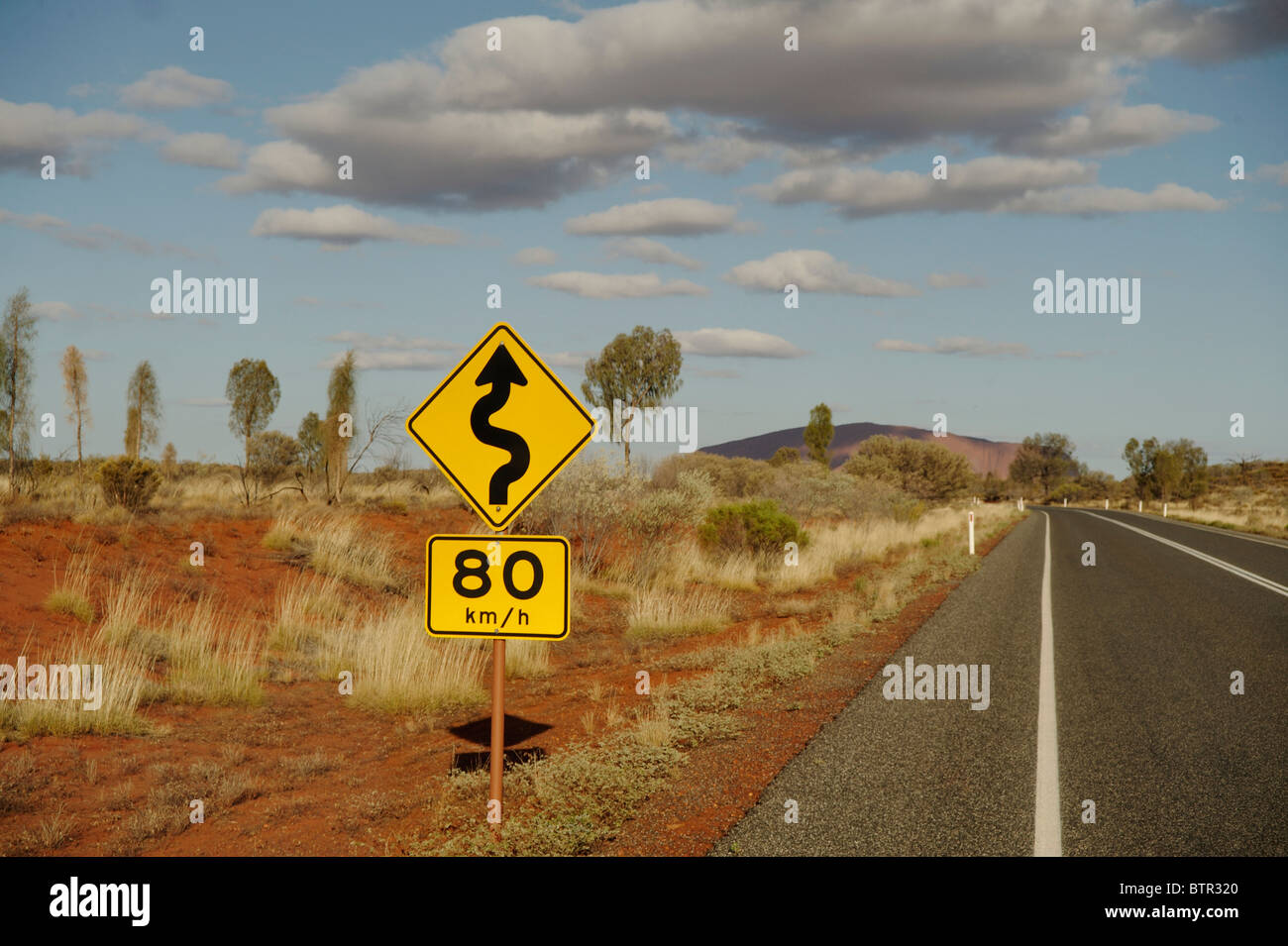 Australia, Northern Territory, Uluru-Kata Tjuta National Park, View of road sign on roadside Stock Photo