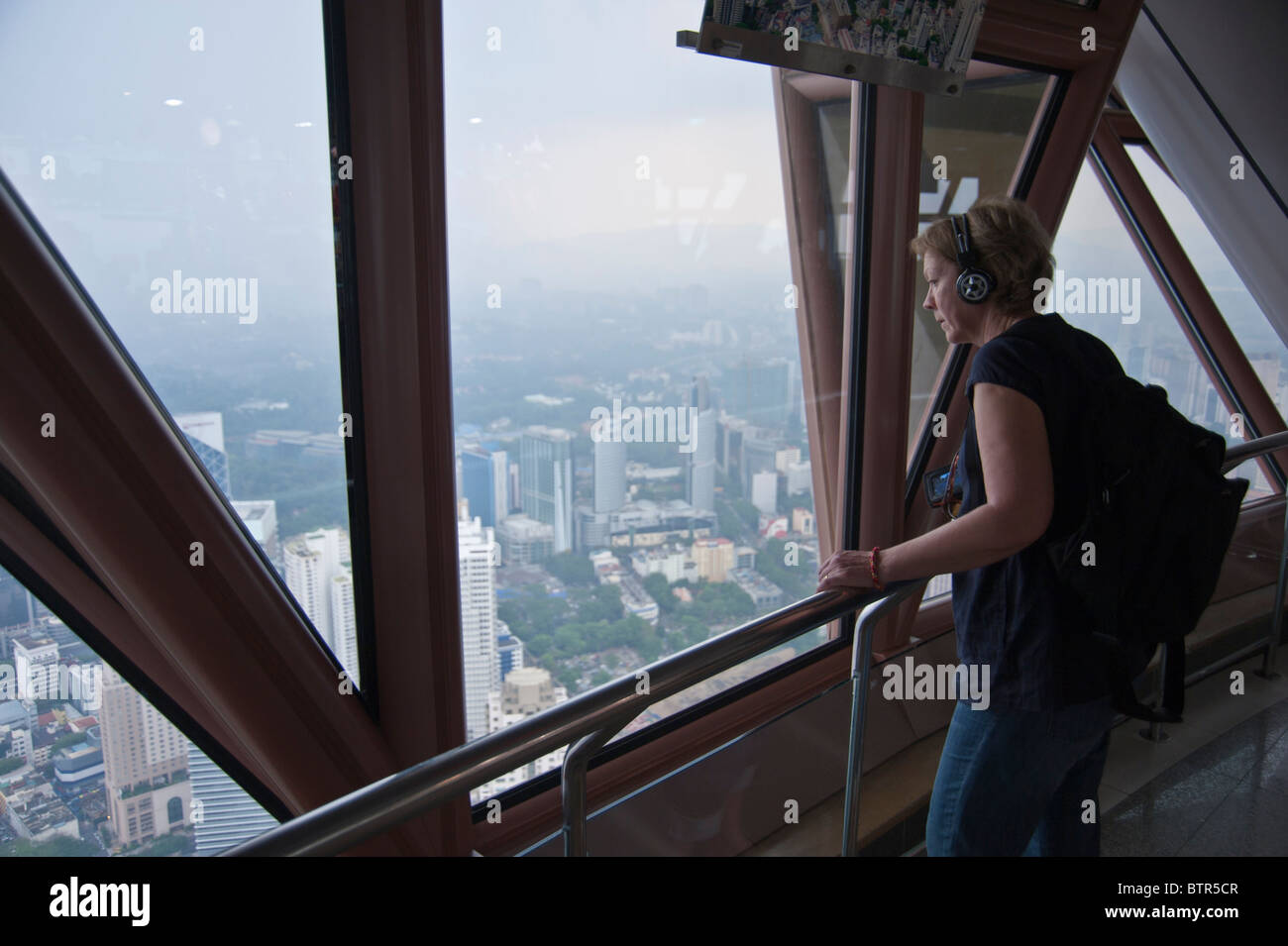 Tourist looking out of the window from the top of KL Tower Kuala Lumpur Malaysia. Wearing headphones listening to - Stock Image