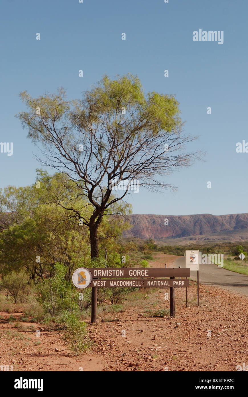 Australia, West MacDonnell National Park, Ormiston Gorge, National park sign and road - Stock Image