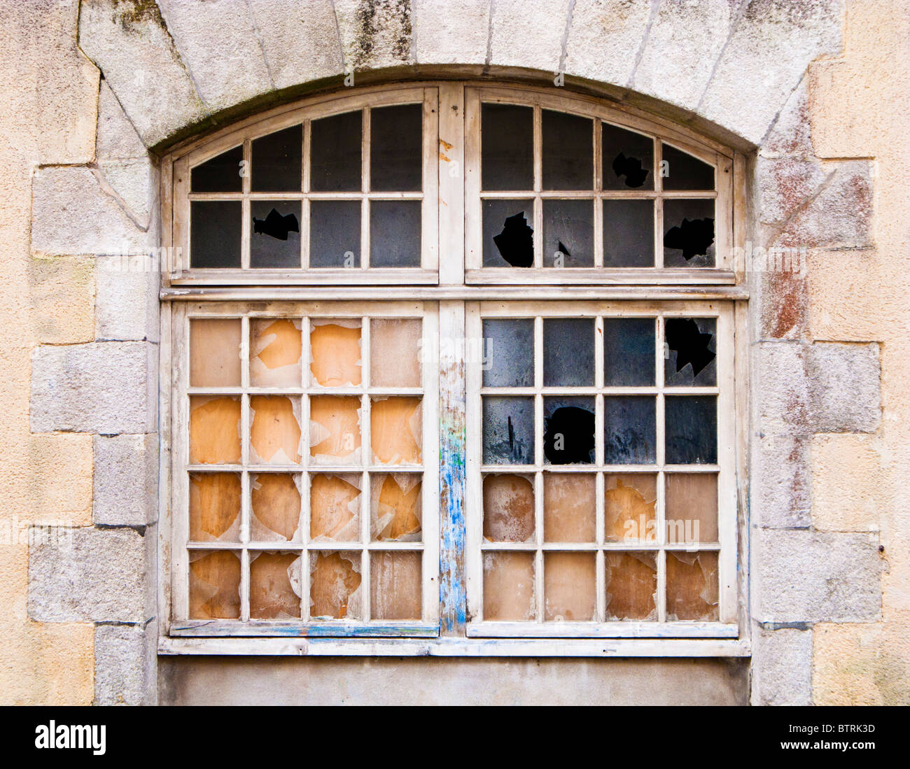 Arched window with broken panes of glass - Stock Image