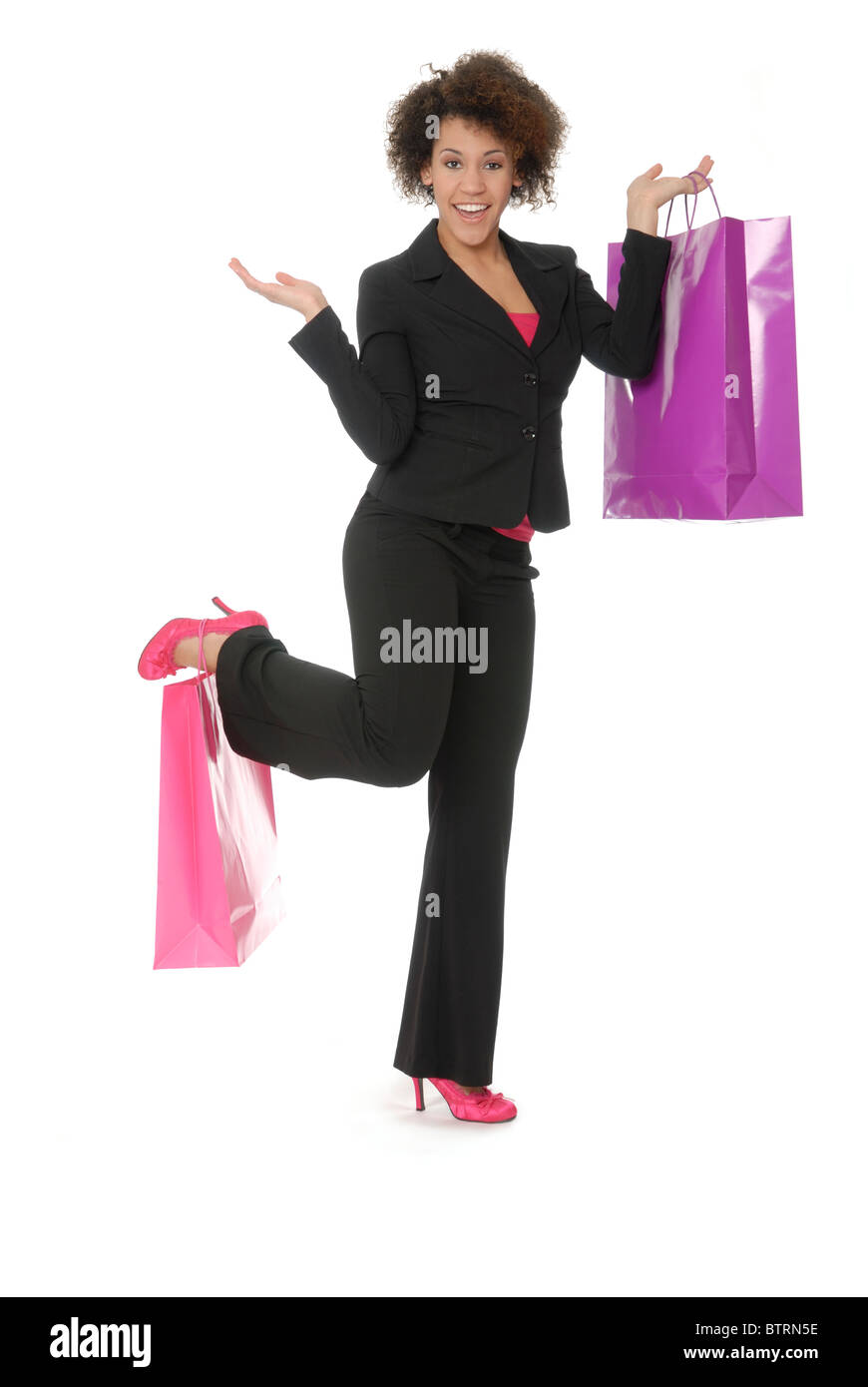 Attractive, enthusiastic young woman shopper, holding one bag in her hand and one on her shoe or foot. Model is - Stock Image