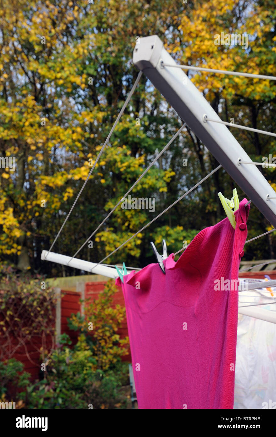 pink cardigan on rotary drier - Stock Image