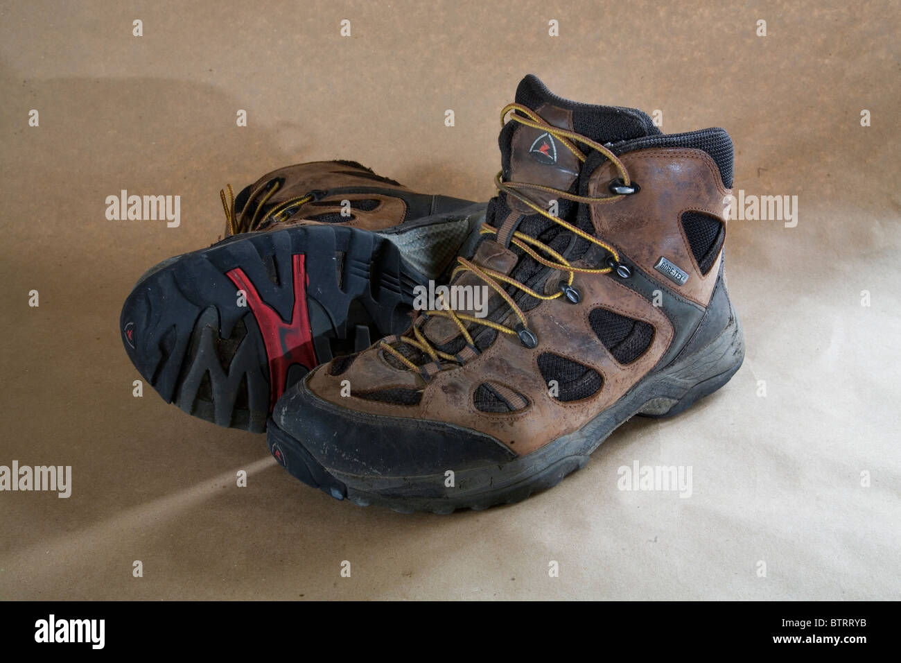 A pair of worn out lace up hiking boots. - Stock Image