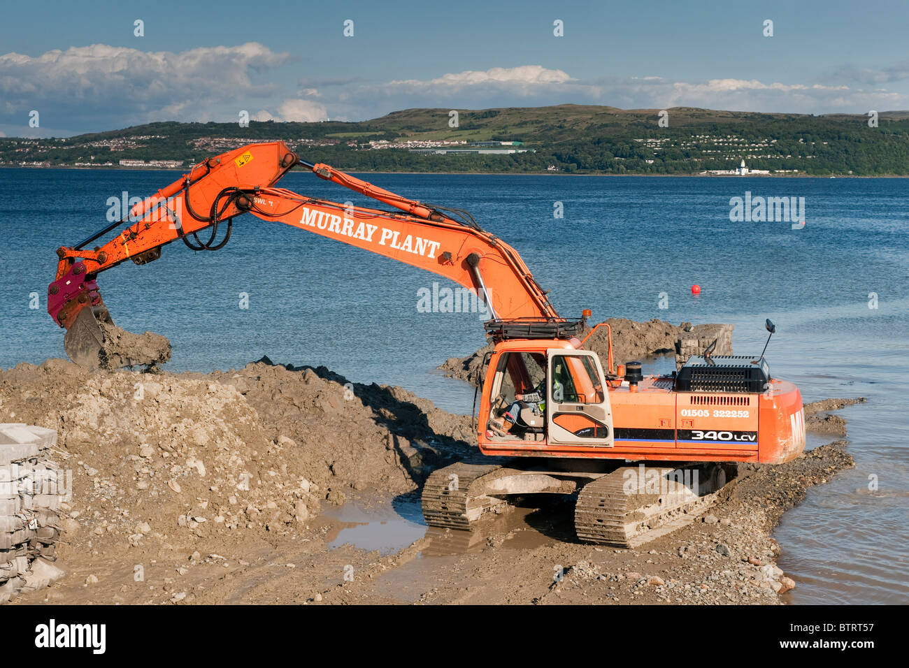 Large digger building sea defences at Dunoon, Argyll. - Stock Image