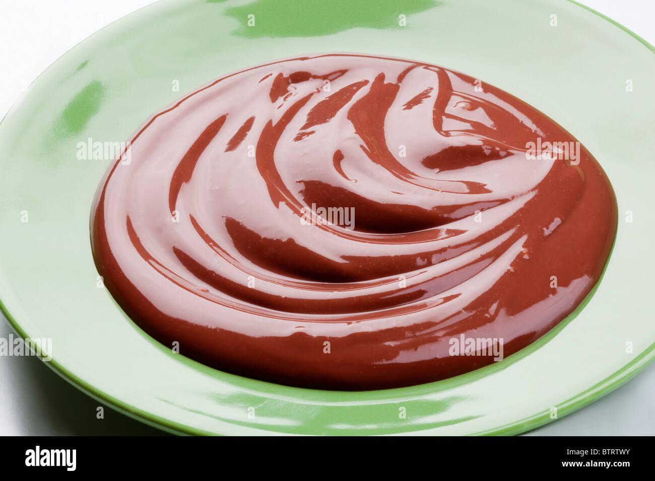Swirl of chocolate cream on a plate - Stock Image