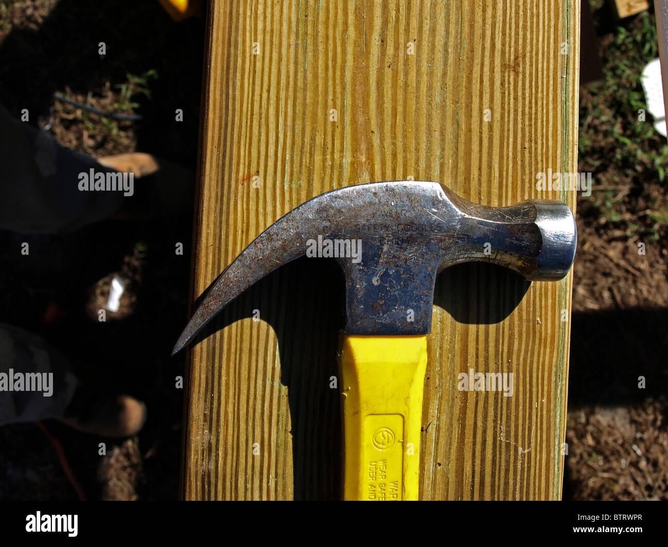 claw hammer construction building yellow head metal handle on wood closeup shadow stud - Stock Image
