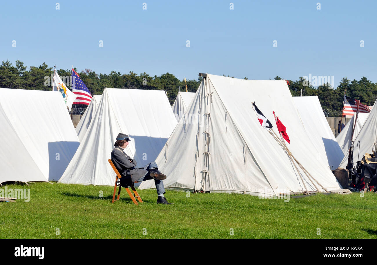 Civil War soldier sitting outside tents of a civil war camp reenactment. - Stock Image