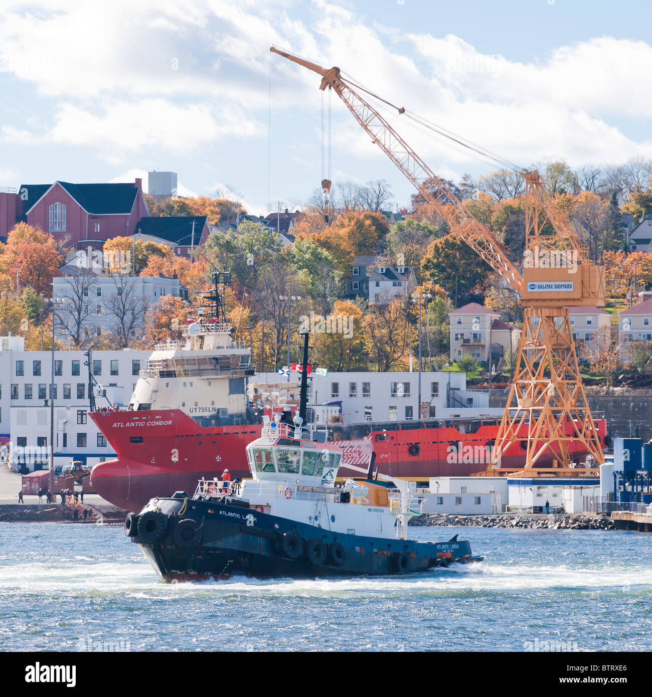 The tug Atlantic Larch turns in front of the rig supplier Atlantic Condor  the Halifax Shipyard in Nova Scotia, - Stock Image