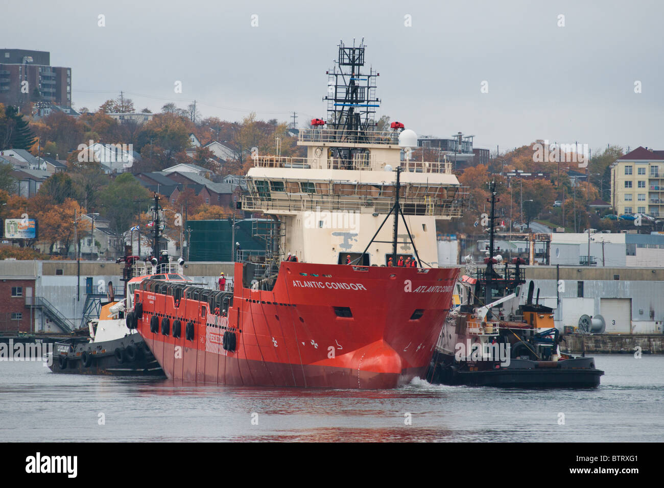Tugs help the rig supplier Atlantic Condor to her fitting out berth at the Halifax Shipyard in Nova Scotia, Canada. - Stock Image