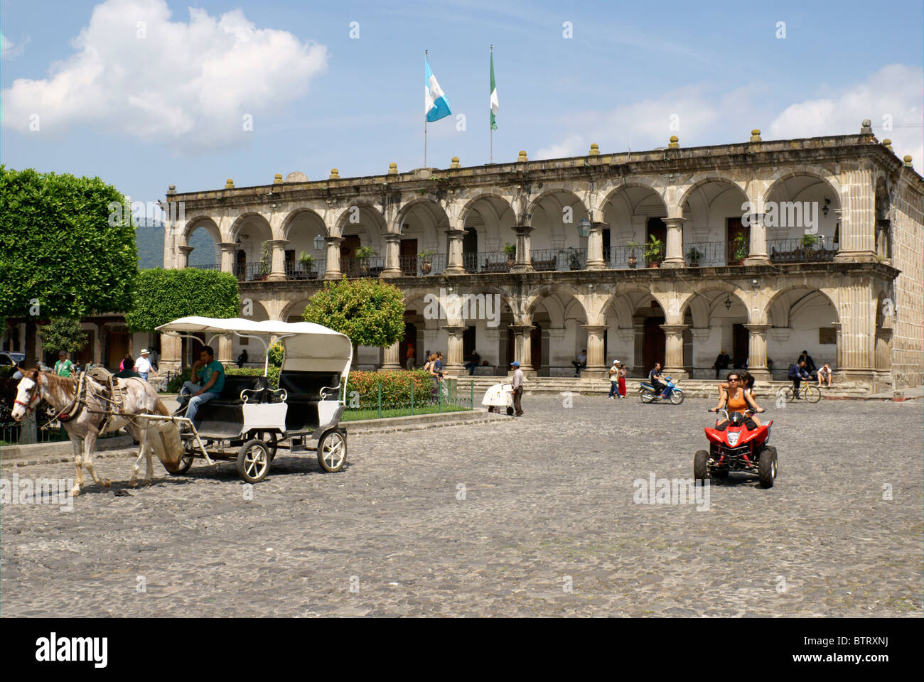 Horse and carriage and ATV in front of Palacio de Ayuntamiento or City Hall facing the Parque Central, Antigua, - Stock Image