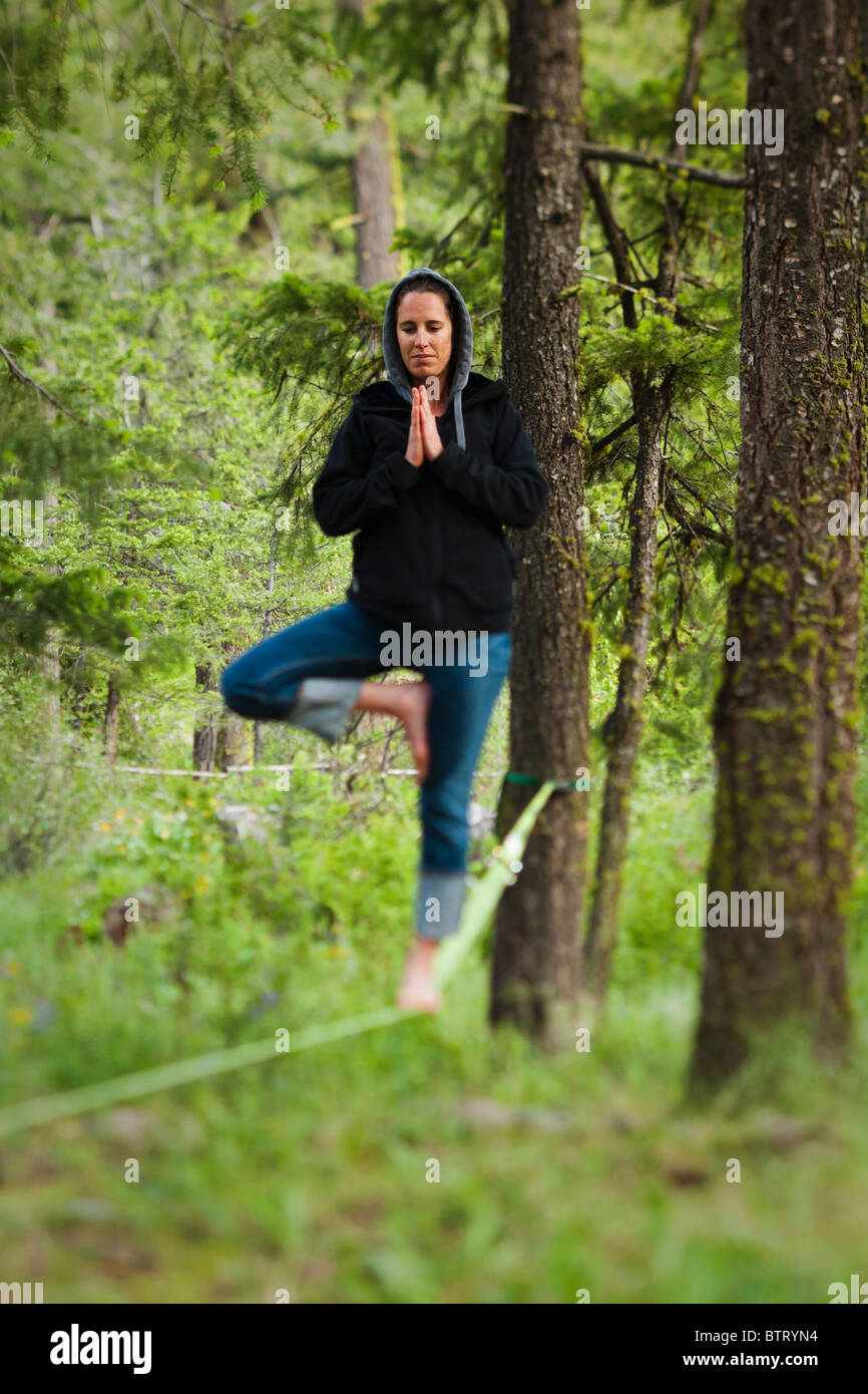 A woman balancing on a slack line in a yoga pose in a forest. - Stock Image