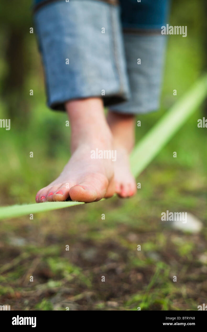 Closeup view of a womans feet on a slack line. - Stock Image