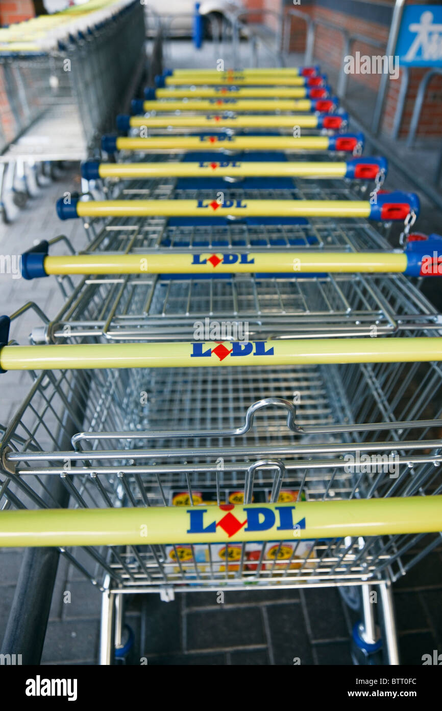 Lidl trolleys lined up outside the store. UK, Britain, Europe. - Stock Image