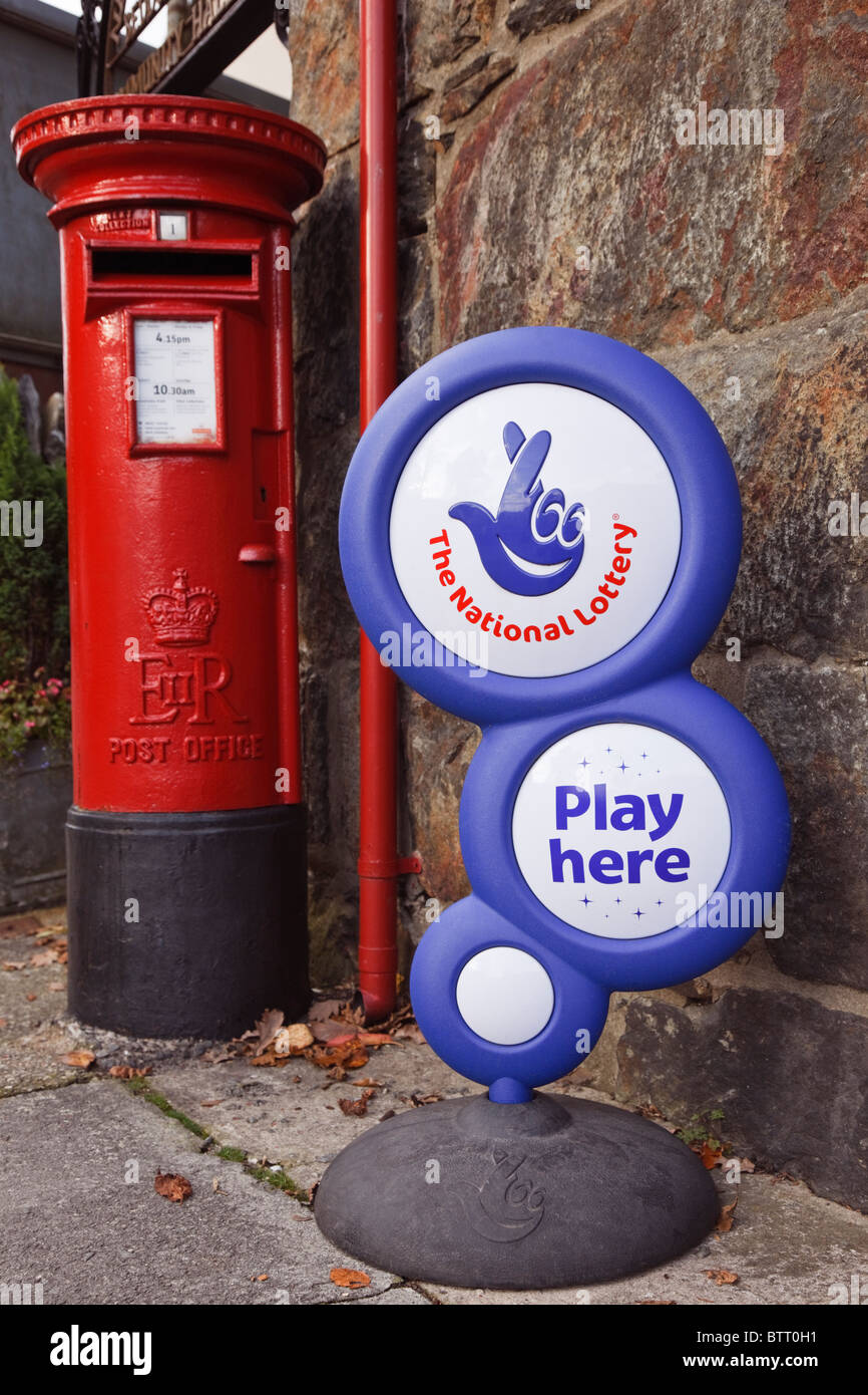 The National lottery 'play here' sign outside a post office with British postbox. UK, Britain. - Stock Image