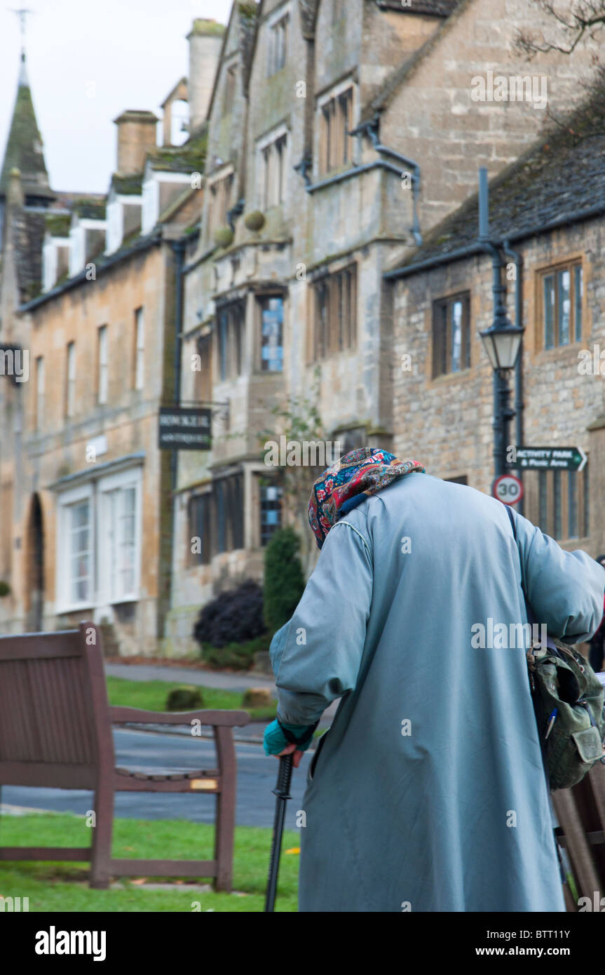 Old lady walks down the road in the Cotswold village of Broadway. Worcestershire, England. - Stock Image
