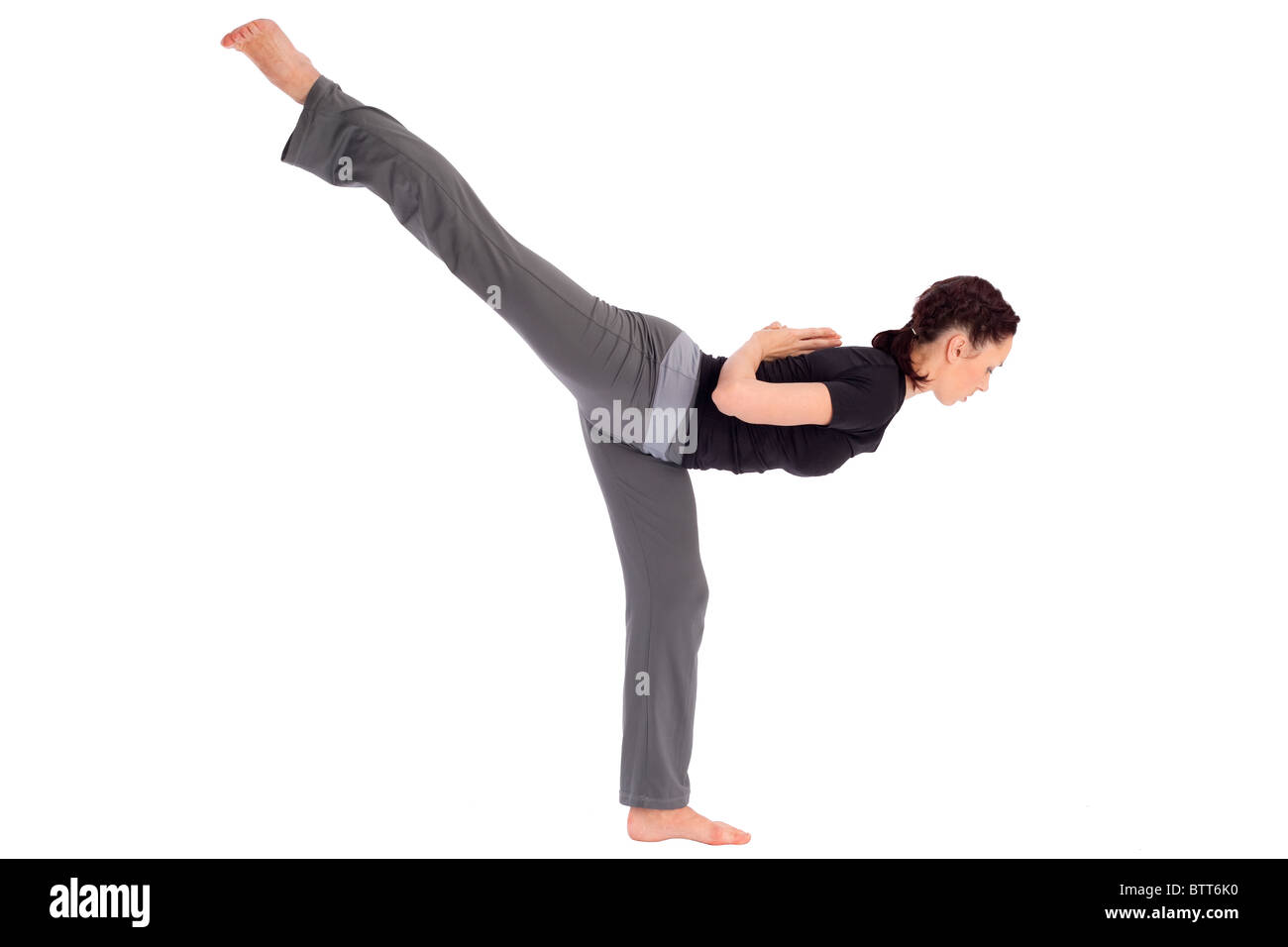 Young fit woman doing yoga asana (Sanskrit name: Eka Pada Hamsa Parsvottanasana), isolated on white background. - Stock Image