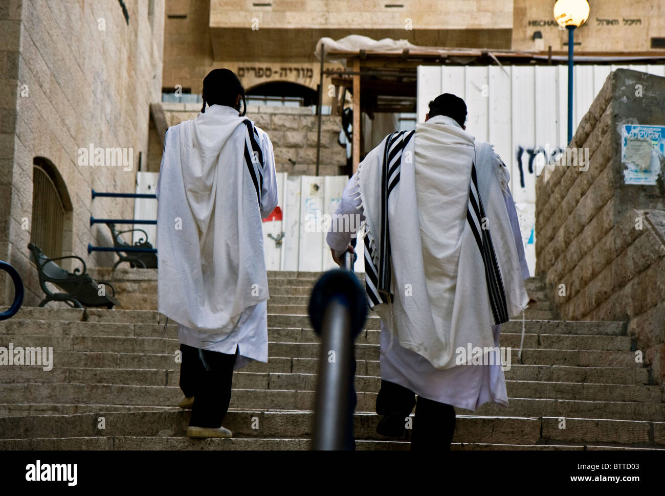 Pair of Jewish religious man with traditional clothes for prier going up the stairs at the old city of Jerusalem - Stock Image