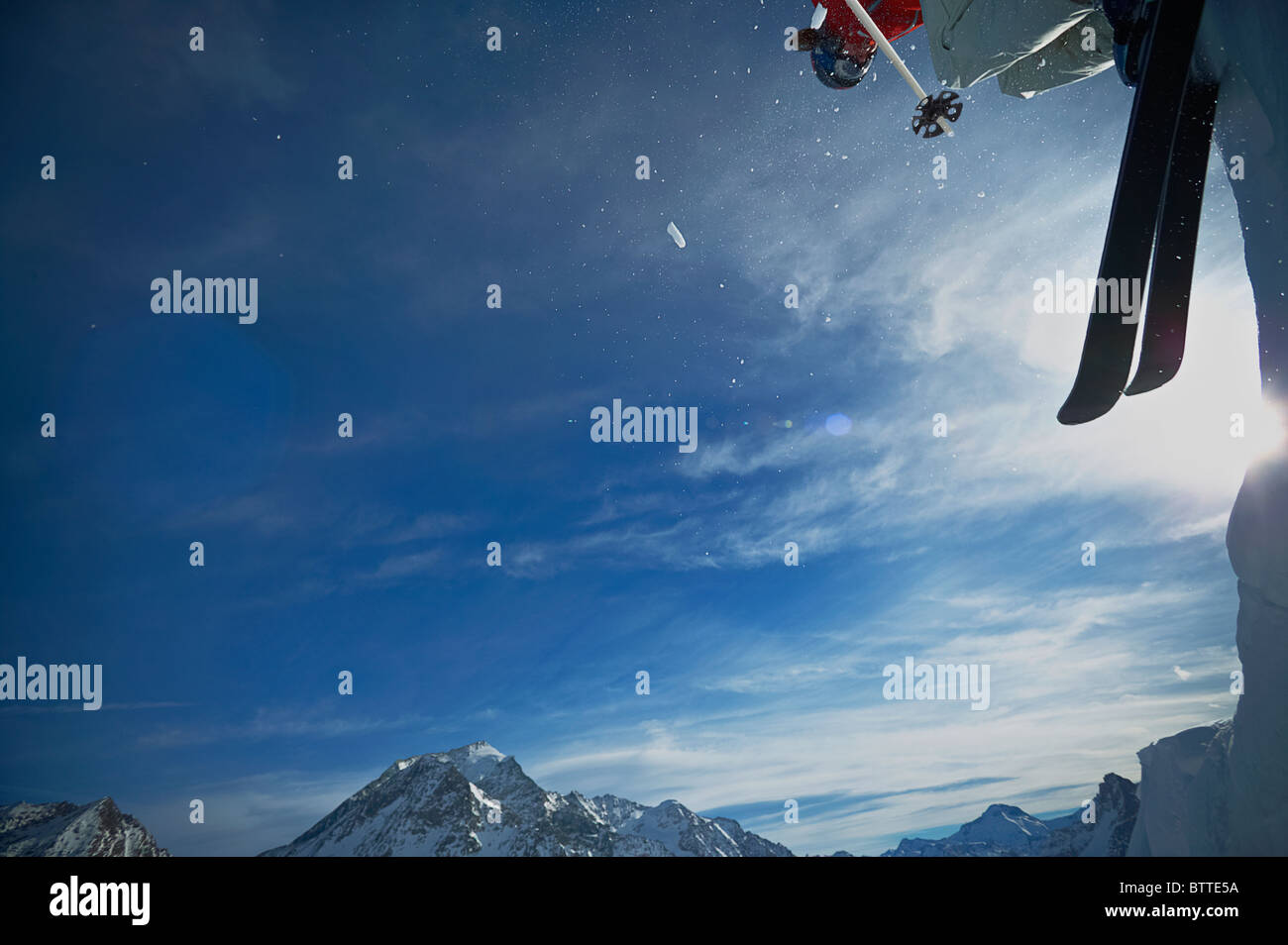 Female skier jumping off a mountain slope, Les Arcs, France. - Stock Image