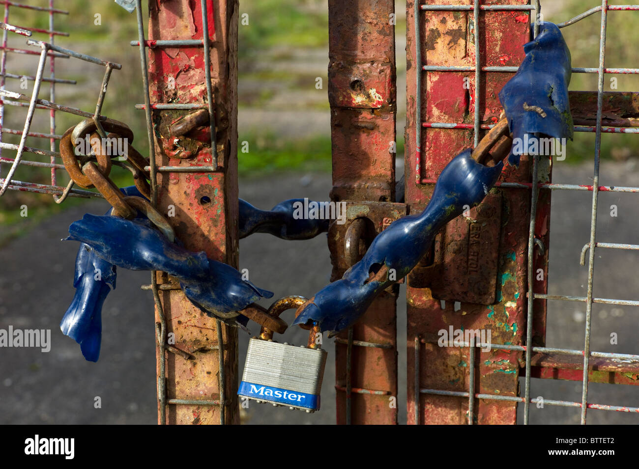 A chained up entrance gate to the wasteland site of a bankrupt business in the recession - Stock Image