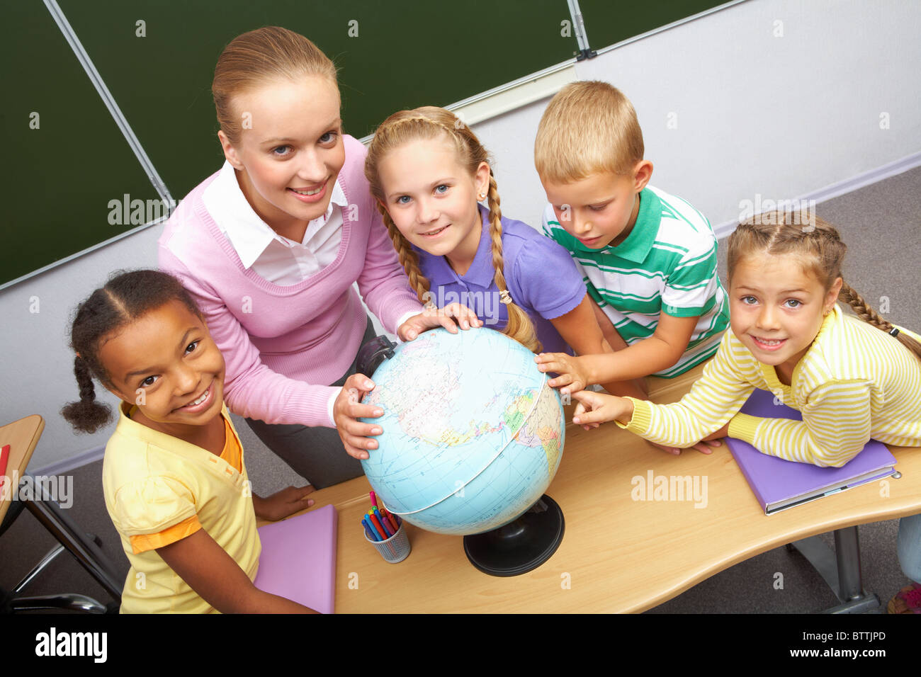 Portrait of pupils and teacher looking at camera with globe on table during geography lesson - Stock Image