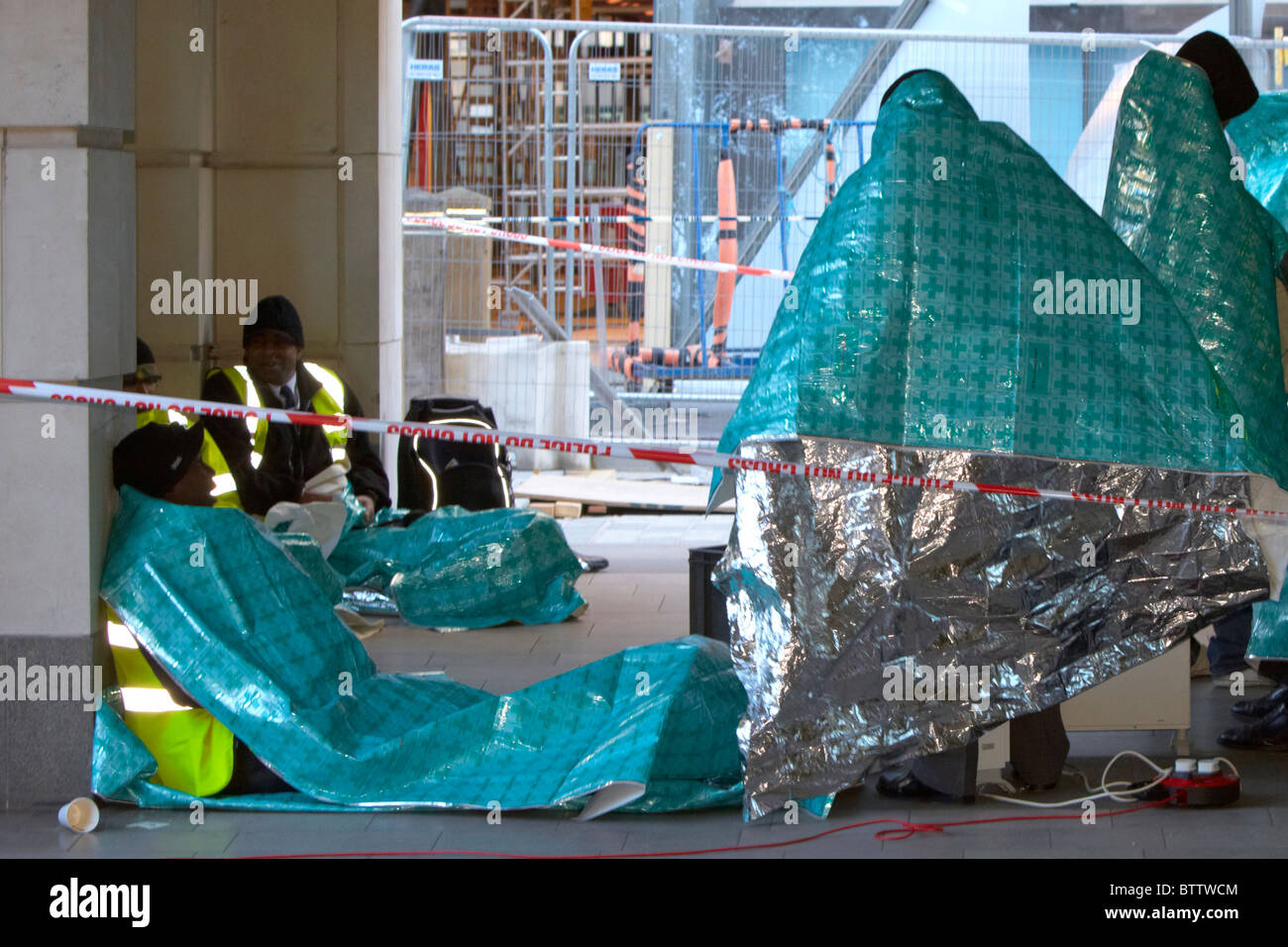 Evacuated office workers use thermal blankets to keep warm after a nearby chemical spill - Stock Image