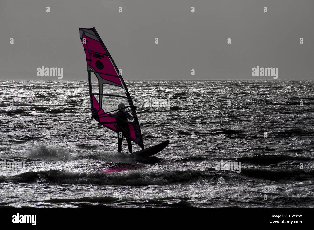 Lone windsurfer silhouetted against grey sky with color of sail enhanced. - Stock Image