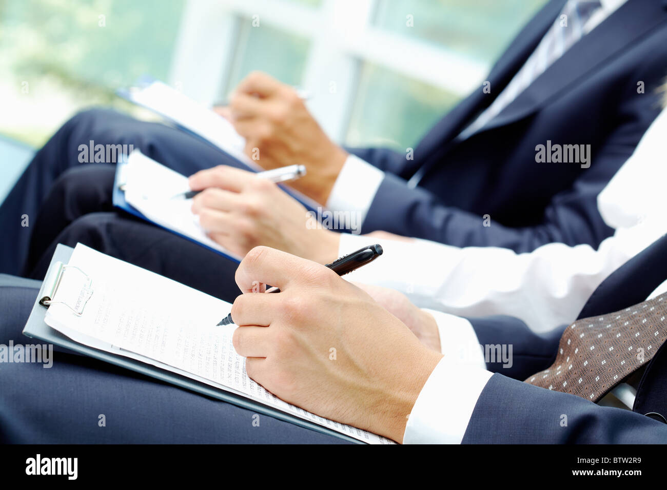 Close-up of business people hands with document writing at lecture - Stock Image